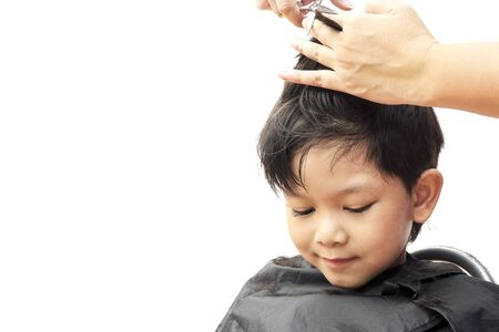 dresser: A boy is cut his hair by hair dresser isolated over white background