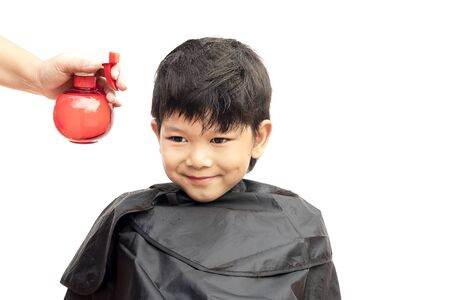 hair dresser: A boy is sprayed his hair by hair dresser isolated over white background Stock Photo