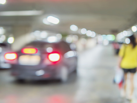 Blurred photo of a woman is walking dangerously in a car parking area Stock Photo