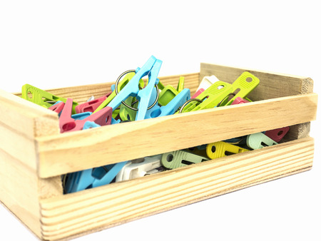 envases plasticos: Colorido clothespins en un contenedor de madera blanca aislado más de blanco