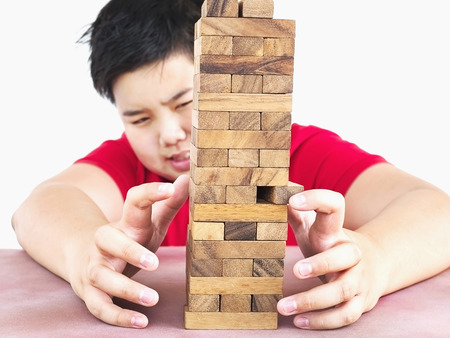 consciously: Asian kid is playing wood blocks tower game for practicing physical and mental skill. Photo is focused at model hands and isolated over white.