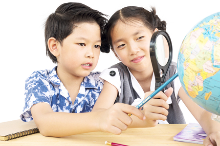Asian kids are studying the globe using magnifier over white background
