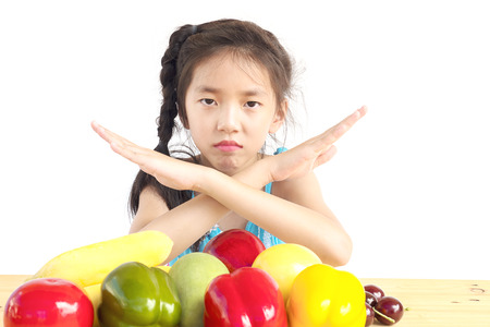 Asian girl is showing dislike vegetable expression over white background
