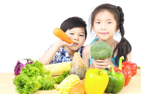 Asian boy and girl showing enjoy expression with fresh colorful vegetables isolated over white background