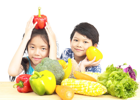 korean salad: Asian boy and girl showing enjoy expression with fresh colorful vegetables isolated over white background