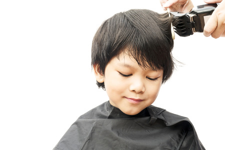 clippers comb: A boy is cut his hair by hair dresser isolated over white background