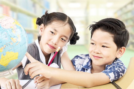 Asian kids are studying the globe in their classroom Stock Photo