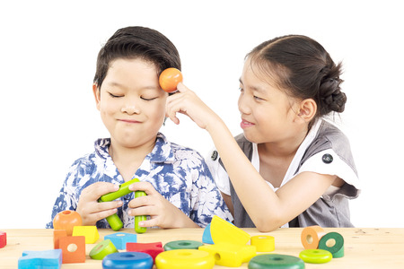 Asian boy and girl are happily playing colorful wood block toy isolated on whit background