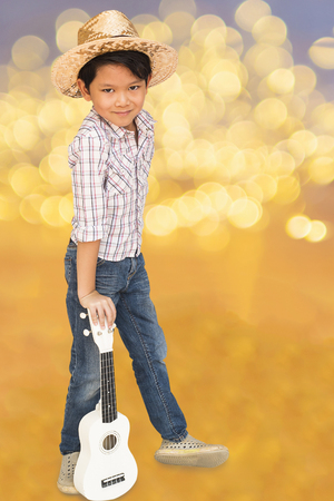 thai musical instrument: Asian boy is standing with ukulele over yellow bokeh background. Photo includes CLIPPING PATH. Stock Photo
