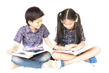 10 and 7 years Asian school girl and boy happily sitting and reading book together isolated over white