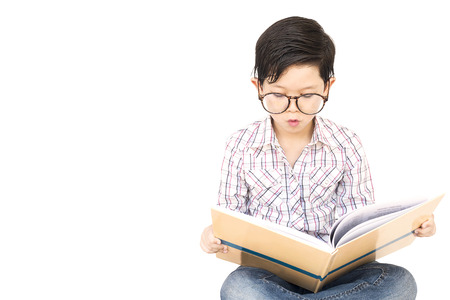 7 year old boys: Seven year old Asian boy is reading a book excitedly isolated over white