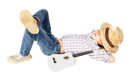 leisurely: 7 years old Asian boy lie leisurely with ukulele isolated over white.