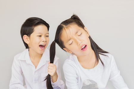 Lovely Asian couple school kids playing together, 7 and 10 years old, over gray background Stock Photo