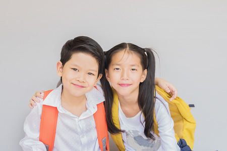 Lovely Asian couple school kids, 7 and 10 years old, over gray background Stock Photo