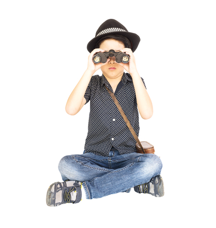 using binoculars: 7 years old Asian traveler boy is sitting and using binoculars isolated on white background