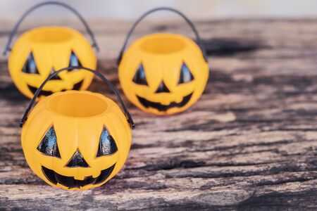 Empty Halloween pumpkin face buckets on old wooden texture
