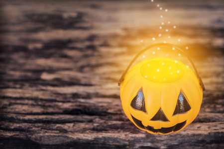 Dark tone photo with of Halloween pumpkin face with warm golden dot evaporate on top of bucket over old wooden texture Stock Photo