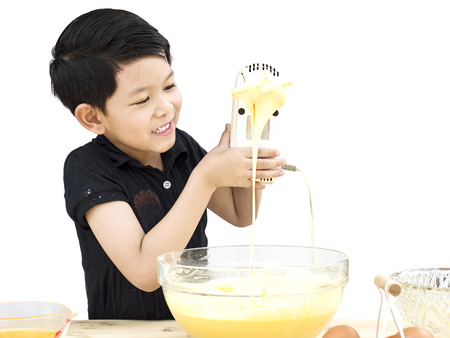 A boy is making cake isolated over white. Photo is focused at his face. Stock Photo