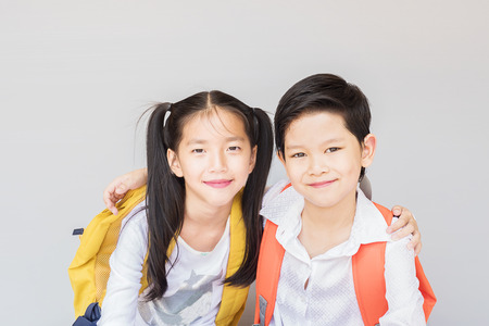 singaporean: Lovely Asian couple school kids, 7 and 10 years old, over gray background Stock Photo