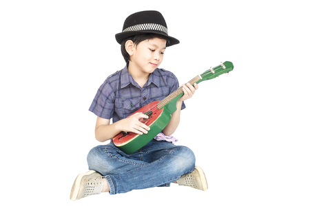 thai musical instrument: 7 years old Asian boy is sitting and playing ukulele isolated over white. Stock Photo