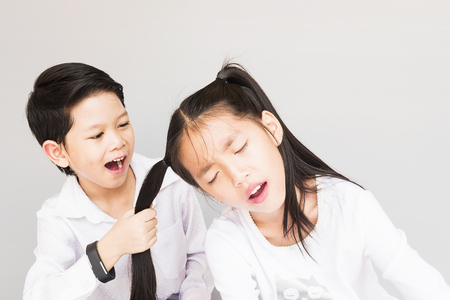 7 year old boys: Lovely Asian couple school kids playing together, 7 and 10 years old, over gray background Stock Photo