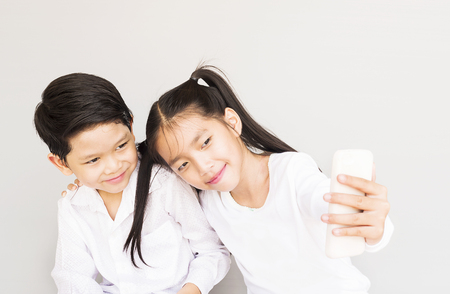 Lovely Asian couple school kids are taking selfie, 7 and 10 years old, over gray background Stock Photo