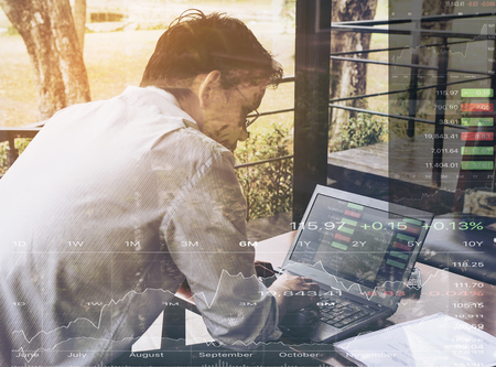 businessman working at his computer: Businessman is working with his computer in coffee shop overlay with stock chart data Stock Photo