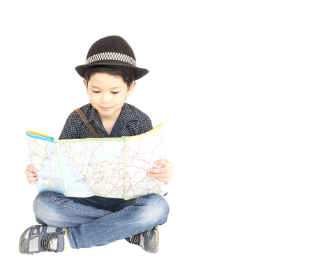 7 years old Asian traveler boy is happily sitting and looking at a map.