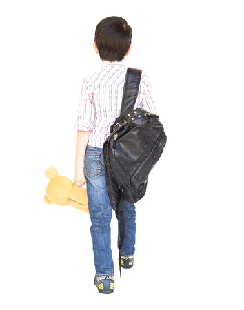 Seven year old Asian boy with a bag is ready to go to school isolated over white