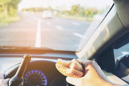 violation: Man eating hotdog with beer while driving a car dangerously Stock Photo