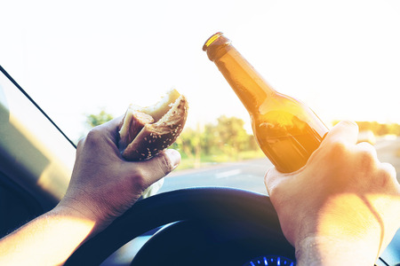 Man eating hotdog with beer while driving a car dangerously Stock Photo