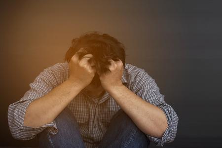 Sad man holding head with hand