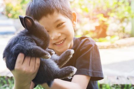 Kid playing lovely baby rabbit 免版税图像