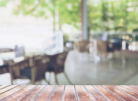Brown wooden terrace foreground over blurred empty restaurant background 写真素材