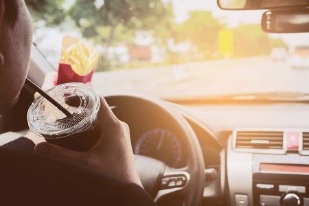 Man driving car while eating French fries and soft drink, right-driving countries