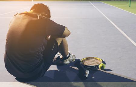 Giocatore di tennis triste seduto nel campo dopo aver perdere una partita Archivio Fotografico - 79722959