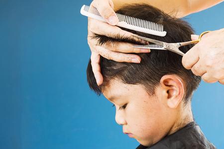 A boy is cut his hair by hair dresser Stock Photo