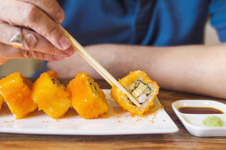 Man eating Maki Sushi