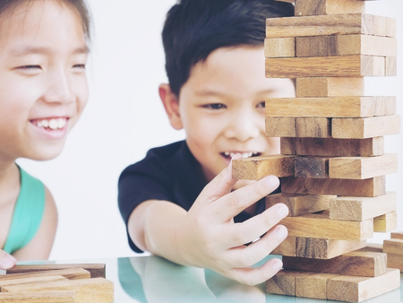 Children are playing a wood blocks tower game for practicing their physical and mental skill Stockfoto
