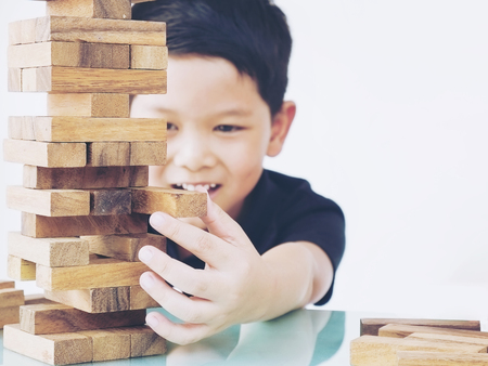 Vintage tone of asian kid is playing wood blocks tower game for practicing physical and mental skill. Photo is focused is hands. Stockfoto