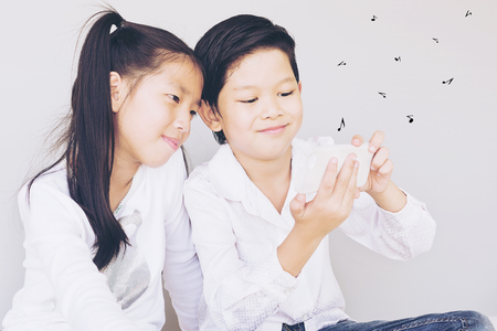 Lovely Asian couple school kids are playing song on mobile phone, 7 and 10 years old, over gray background