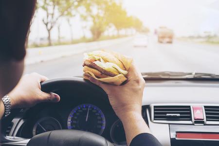 Man driving car while eating hamburger