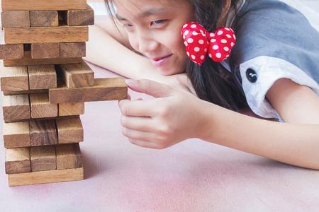 Het Aziatische jonge geitje speelt het spel van de houtsnedentoren voor het praktizeren van fysieke en geestelijke vaardigheid