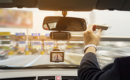 Man driving car using navigator and holding electronic toll collection system device