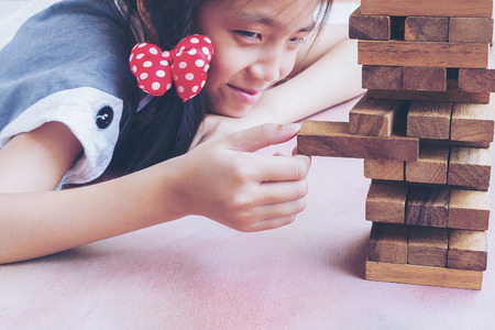 Asian kid is playing wood blocks tower game for practicing physical and mental skill