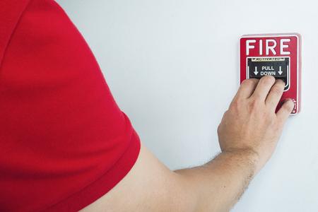 남자 화재 경보 핸드 스테이션을 밀어 그의 손에 도달입니다