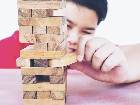 Asian kid is playing wood blocks tower game for practicing physical and mental skill. Photo is focused at model hands and isolated over white.