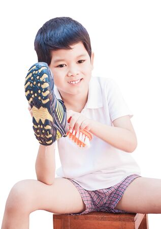 A boy is happily cleaning his shoe isolated on white background