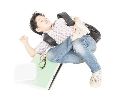Tired eight years boy sleeping his school belonging isolated over white