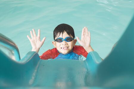 Asian happy kid playing slider in swimming pool